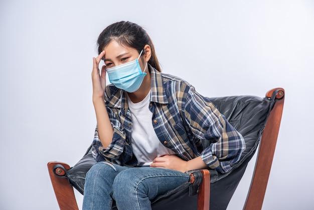 Die frau war krank, setzte sich auf einen stuhl und berührte ihren kopf mit der hand.