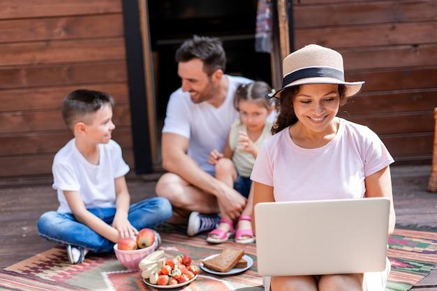 Die frau wird vom familienurlaub abgelenkt, arbeitet durch das w-lan mit einem laptop und hält ein arbeitsmeeting in zoom ab, überwacht die arbeit ihrer firma in den ferien
