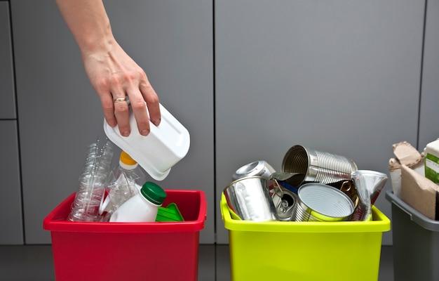 Die frau wirft den plastikbehälter in den einen von vier behältern, um den müll zu sortieren