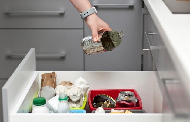 Die frau wirft die blechdose in einen von vier behältern, um den müll zu sortieren