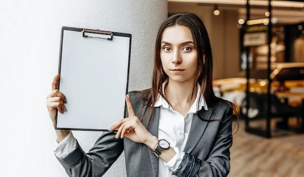 Die frau zeigt ein leeres blatt papier mit informationen auf dem tablett