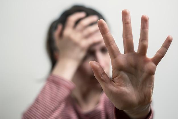 Die frau zeigt nein von hand, lehnt belästigungen ab. das mädchen bedeckt ihr gesicht.
