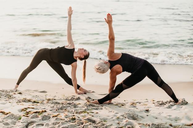 Die frauen, die eignung tun, trainieren in der synchronisierung, die in yoga asana auf dem strand nahe meer aufwirft