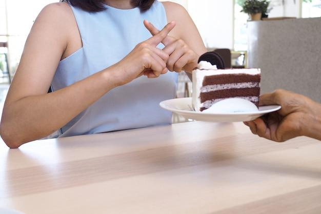 Die frauen drückten mit den leuten auf den kuchenteller. essen sie keine desserts zur gewichtsreduktion.