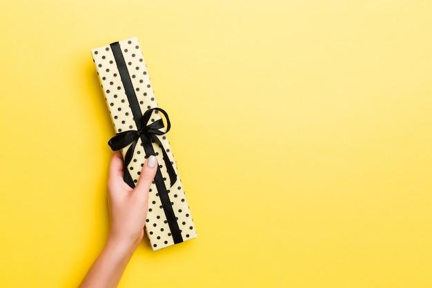 Die frauenarme, die geschenkbox mit farbigem band auf gelbem tabellenhintergrund, draufsicht und kopienraum für sie halten, entwerfen