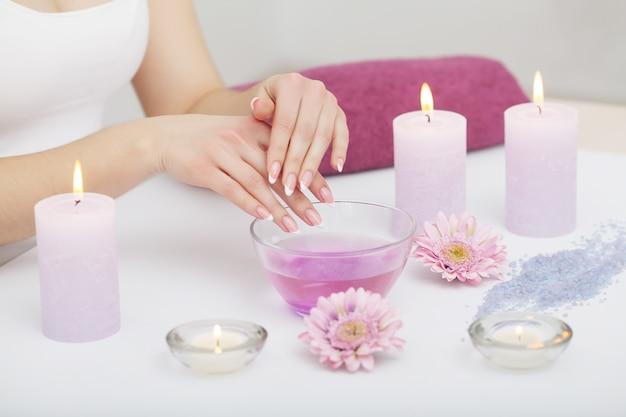 Die frauenhände, die eine hand empfangen, scheuern schale durch einen kosmetiker im schönheitssalon