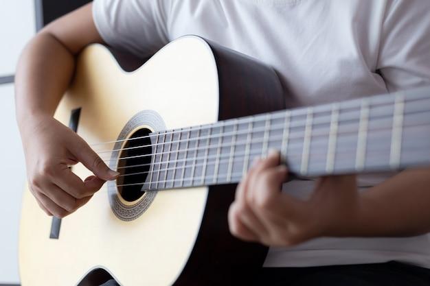 Die frauenhände, die klassische akustikgitarre der musiker des jazz und der einfachen hörenden art spielen, wählen flache schärfentiefe des fokus aus