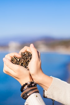 Die frauenhände, die kleine steine halten, bilden herzform