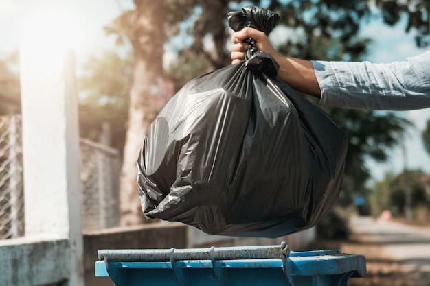 Die frauenhand, die abfallschwarzbeutel hält, setzte sich herein, um abfall zu machen