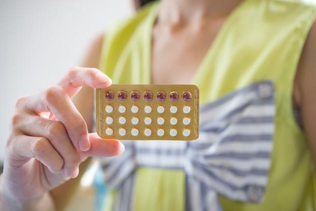 Die frauenhand, die eine empfängnisverhütende platte hält, verhindern schwangerschaft