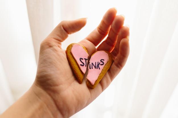 Die frauenhand, die lebkuchenplätzchen eines defekten herzens verziert mit rosa fondant mit der mitteilung hält, stinkt. herzschmerz-konzept.
