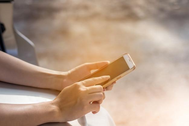Die frauenhand, die smartphone mit großem leerem bildschirm und modernem rahmen hält, entwerfen weniger