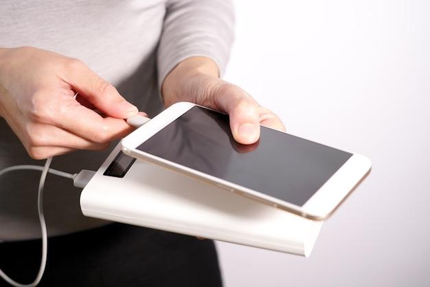 Die frauenhand hält das telefon und ladegerät, powerbank und smartphone verbindet