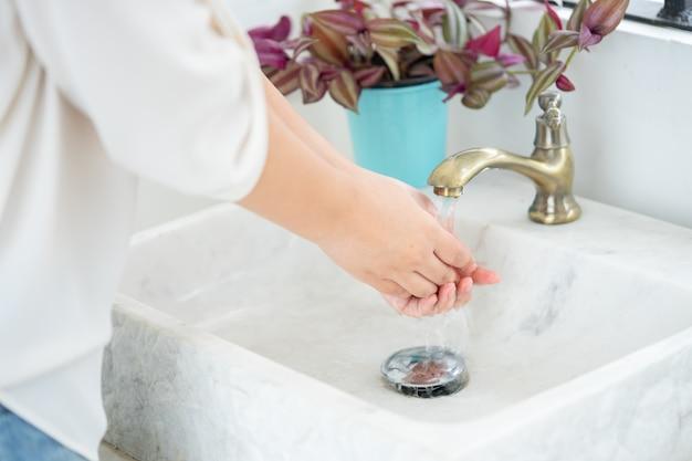 Die frauenhand wird den wasserhahn öffnen, um sich die hände zu waschen. sauberkeit zu pflegen