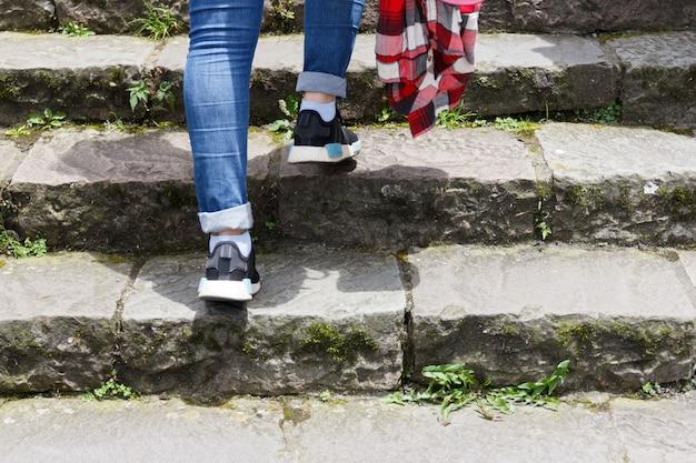 Die frauenjeans und turnschuhe gehen die treppe hinauf.