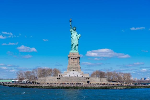 Die freiheitsstatue in new york city. freiheitsstatue mit blauem himmel über dem hudson auf insel. grenzsteine von unterem manhattan new york city.