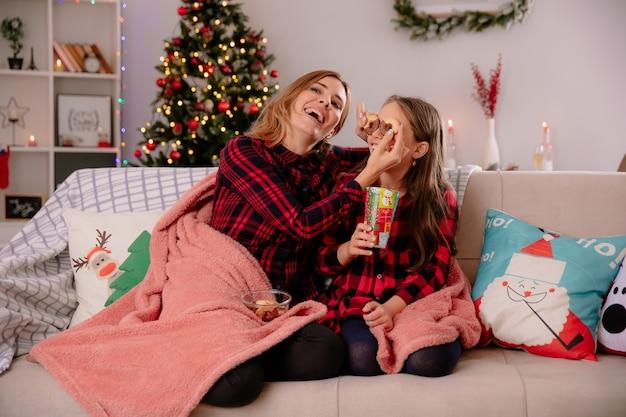 Die freudige mutter bedeckt die augen der tochter mit keksen, die auf der mit einer decke bedeckten couch sitzen und die weihnachtszeit zu hause genießen