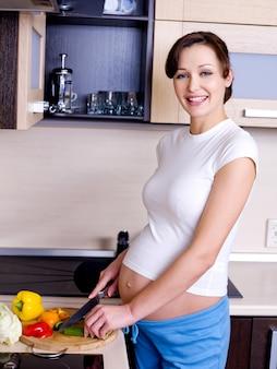 Die freudige schwangere frau bereitet sich auf das essen vor