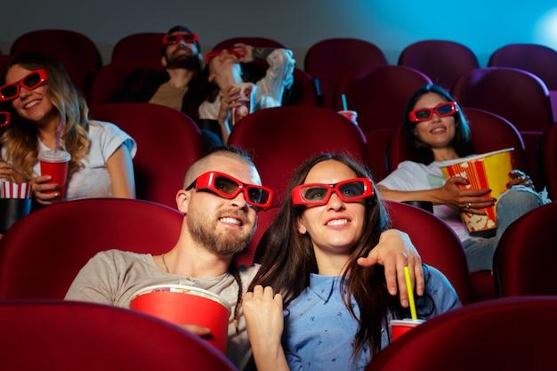 Die freunde, die im kino sitzen, passen film auf, popcorn und trinkwasser essend.