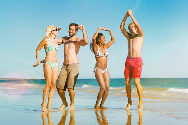 Die freunde springend auf ozeanstrand in den ferien