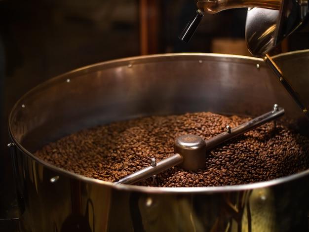 Die frisch gerösteten kaffeebohnen aus einem kaffeeröster mischen sich im kühlzylinder