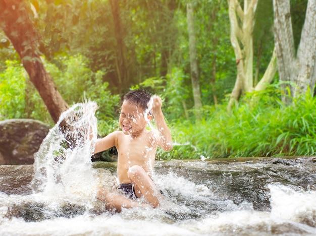 Die frische der kinder, die im wasserfall spielen glückliches kindjungenspielen