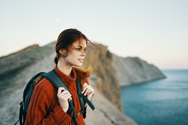 Die frische luft der naturberge und ein junger reisender mit einem rucksack und einem pullover ruhen sich in der nähe des aus