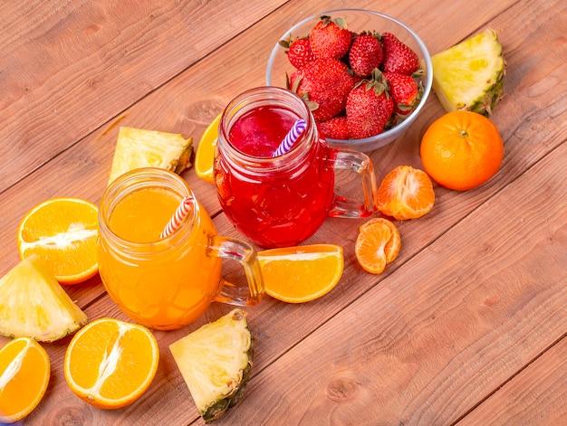 Die frischen erdbeer- und orangencocktails mit früchten auf einem hölzernen rustikalen hintergrund.