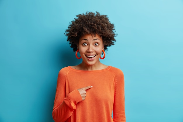 Die fröhlich überraschte junge hübsche afroamerikanerin zeigt auf sich selbst und fragt, wen ich im großen und ganzen lächle, ohne erwartet zu haben, ausgewählt zu werden