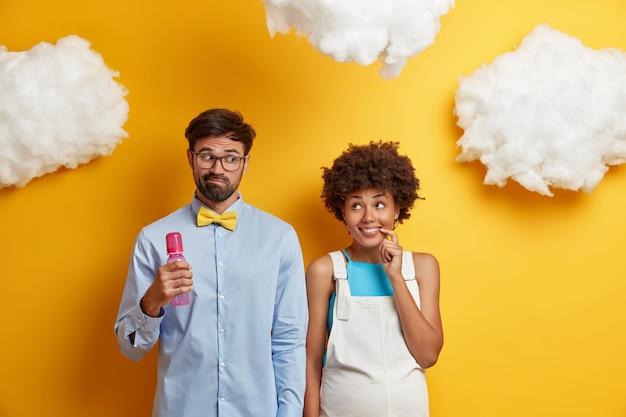 Die fröhliche afroamerikanische schwangere frau hat einen blick auf den ehemann, der eine flasche in der hand hält, um sich darauf vorzubereiten, eltern zu werden