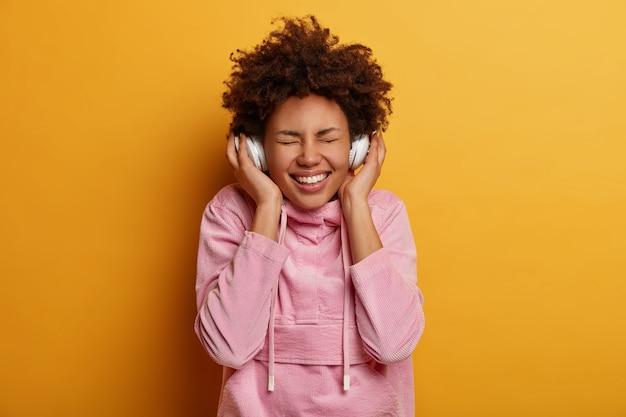 Die fröhliche frau mit den lockigen haaren genießt jedes lieblingslied, hört musik in stereokopfhörern, schließt die augen und lächelt breit, inspiriert von großartiger musik, gekleidet in freizeitkleidung, steht drinnen
