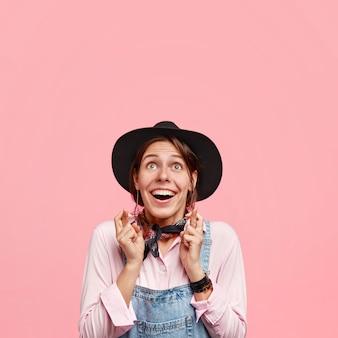 Die fröhliche gärtnerin schaut positiv nach oben, hat ein breites strahlendes lächeln, drückt die daumen für viel glück, trägt einen eleganten schwarzen hut und eine latzhose, isoliert über der rosa wand. menschen und wunschkonzept