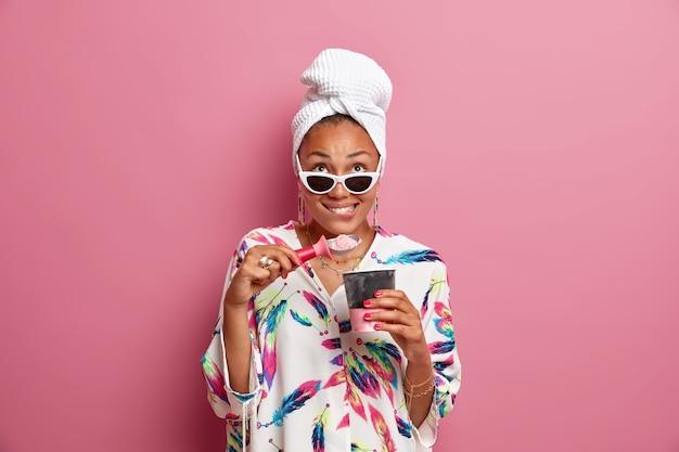Die fröhliche hausfrau, die sich oben konzentriert, isst leckeres kaltes eis aus dem eimer, trägt eine sonnenbrille aus seidenbademantel umwickeltes handtuch auf dem kopf isoliert über rosafarbener wand. häuslicher stil