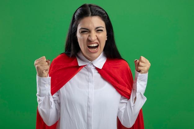 Die fröhliche junge superfrau, die ihre fäuste hochlegt, genießt den sieg und das lächeln, das auf der grünen wand isoliert betrachtet