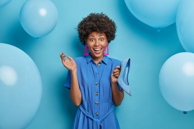 Die fröhliche modedame kleidet sich in ein blaues kleid und hält schuhe mit hohen absätzen, die zu ihrem outfit passen, bereitet sich auf eine themenparty vor, kauft kleidung, ist ein shopaholic, isoliert über einer dekorierten wand. frauen und stil