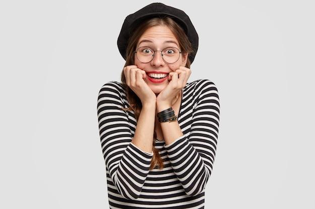 Die fröhliche pariserin berührt das kinn mit beiden händen, hat ein strahlendes lächeln, einen fröhlichen gesichtsausdruck und ist in lässige kleidung im französischen stil gekleidet