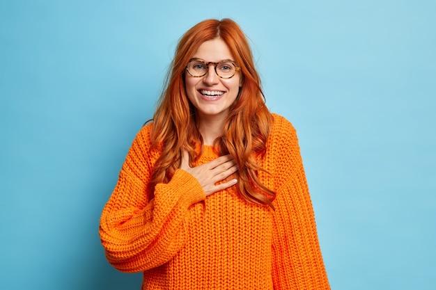 Die fröhliche rothaarige junge frau kichert positiv, als sie hört, dass lustige nachrichten die hand auf der brust halten. sie fühlt sich sehr glücklich, trägt eine brille und einen orangefarbenen strickpullover.