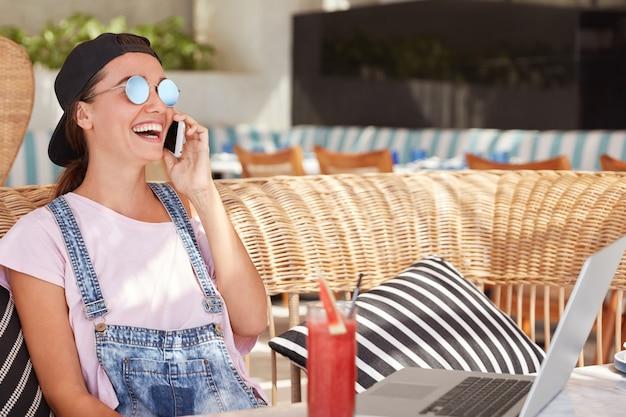 Die fröhliche, stilvolle hipster-frau trägt eine modische, trendige sonnenbrille, eine mütze und einen jeansoverall, unterhält sich angenehm per handy, sitzt auf einem bequemen sofa vor dem café-interieur und trinkt einen cocktail