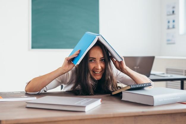 Die fröhliche studentin versteckt ihren kopf unter dem buch unter dem buch.
