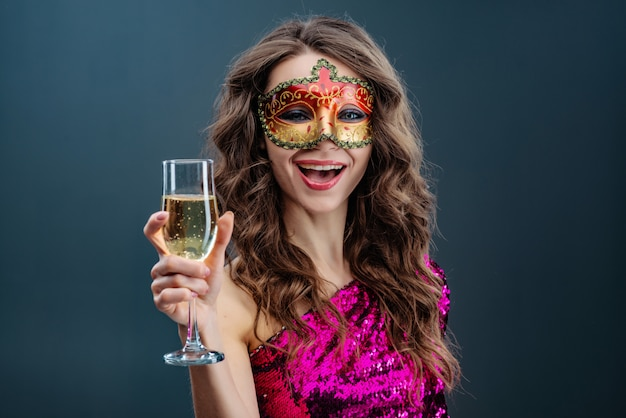 Die frohe frau, die venetianische karnevalsmaske trägt, lächelt breit gegen blauen hintergrund
