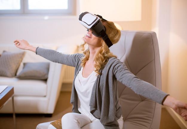 Die frohe junge frau, die zu hause computerspiele mit virtueller realität spielt, googelt