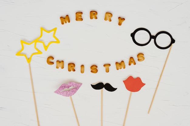 Die frohen weihnachten der wörter geschrieben von den plätzchenbuchstaben und von den maskerademasken.