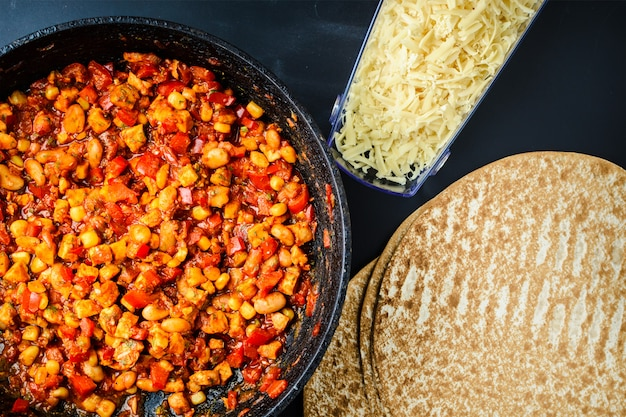 Die füllung für mexikanische quesadilla, fajito oder buritto auf die tortilla legen.