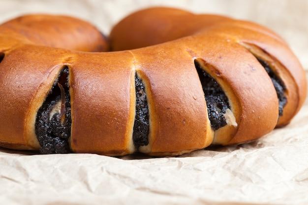 Die füllung von mohn und eiern in einem dessertbrötchen mit frischem brötchen mit einer schwarzen füllung von mohn