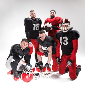 Die fünf american-football-spieler posieren mit ball
