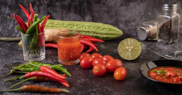 Die für den salat verwendeten zutaten sind tomaten, paprika, limette und bitterer kürbis.