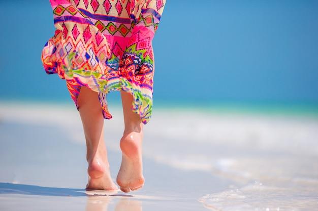 Die füße der frau auf dem weißen sand setzen im seichten wasser auf den strand