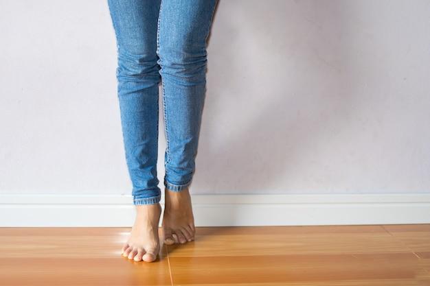 Die füße der frau stehen auf zehenspitzen mit blauem baumwollstoff