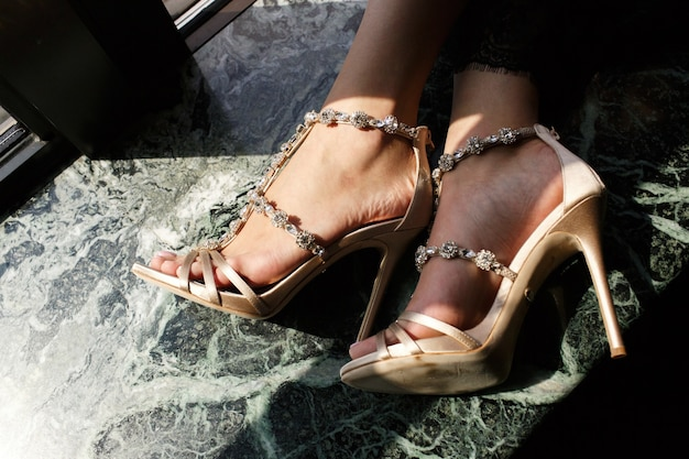 Die füße der zarten frau in den eleganten schuhen auf marmorfensterbrett