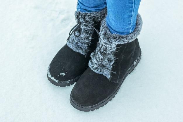 Die füße des kindes in jeans und warmen stiefeln im schnee. schöne und praktische damen winterschuhe.